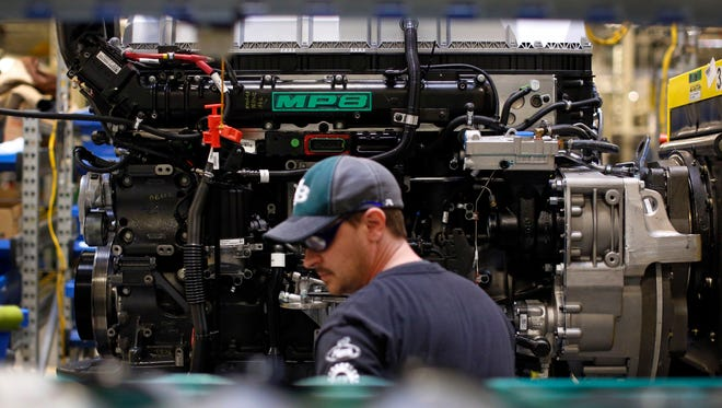 Ed Carbaugh prepares to install parts on a truck engine on an assembly line at Volvo Trucks' powertrain manufacturing facility in Hagerstown, Md. in March 2014.