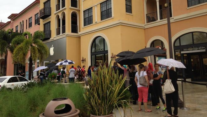 Customers lined up Friday in the rain outside the Apple store at Coconut Point in Estero for the iPhone 6 and iPhone 6 Plus.