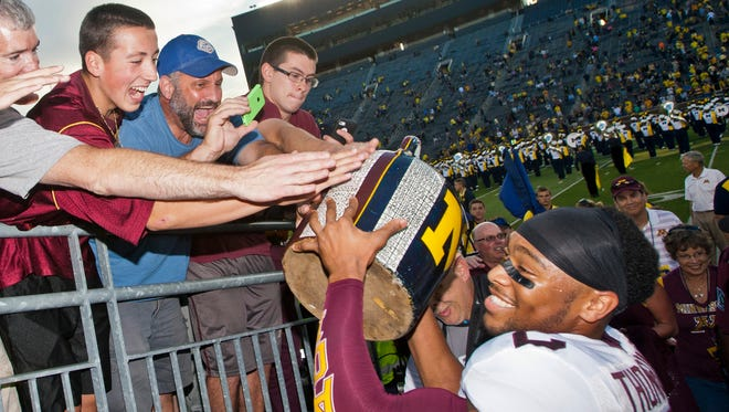 Minnesota fans reach to touch the Little Brown Jug trophy held up by Minnesota defensive back Cedric Thompson, right, after beating Michigan in Ann Arbor on Sept. 27, 2014.