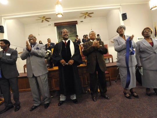 Church members applaud after the Rev. Eddie Jordan cuts a ribbon signifying the re-opening of the New Light Baptist Church sanctuary Sunday. A storm blew the roof off Dec. 12, 2015.