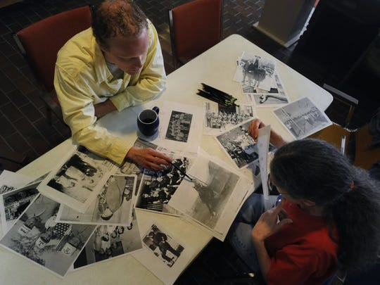 "Daniel Schlegel, Jr., the executive director of the Scurry County Museum, looks over copies of old photographs in the museum's collection with Cindy Sharp Feb. 17, 2011. Schlegel created a program called ""Curatin' and Coffee"" to invite community members to assist them in identifying people in the photographs."