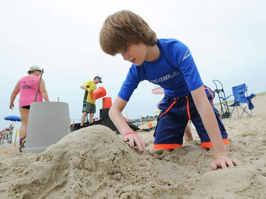 SANDCASTLE CONTEST: Nathan Oltman, 12, of Bethany Beach, Del., works on his sandcastle at the 35th annual sandcastle contest at the Delaware Seashore State South Inlet Park.