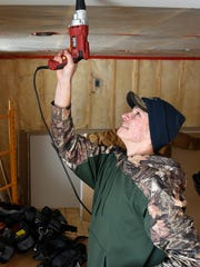 Technical High School student Mitch Koenig attaches drywall in the living room of a new home being built by students Wednesday, Jan. 20.