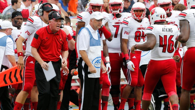 Louisville head coach Bobby Petrino cheers on his team during the first half of an NCAA college football game in Charlottesville, Va., Saturday, Sept. 13, 2014. (AP Photo/Steve Helber)
