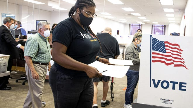 """Sherema Douglass casts her ballot during on the first day of early voting at the Sangamon County Complex, Thursday, September 24, 2020, in Springfield, Ill. """"Due to the pandemic and the unprecedented times and with the things at stake politically right now for our county I think it's really important to get it done early,"""" said Douglass. Early voting will be available at the Sangamon County Complex up until Election Day, check www.sangamoncountyclerk.com for a specific schedule of days and times."""
