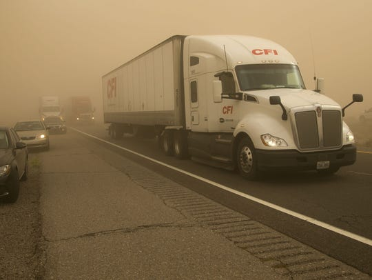 Some vehicles pull over as others drive through a dust