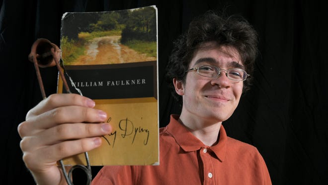 "Battle Ground Academy senior Benjamin Ball holds William Faulkner's ""As I Lay Dying"" and a Bunsen burner lighter. The two items represent Ball's love for literature and math and science."