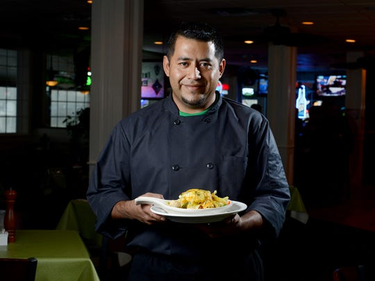 Irish Eyes chef Juan Escamilla holds the restaurant's Seafood Shepherd's Pie dish.