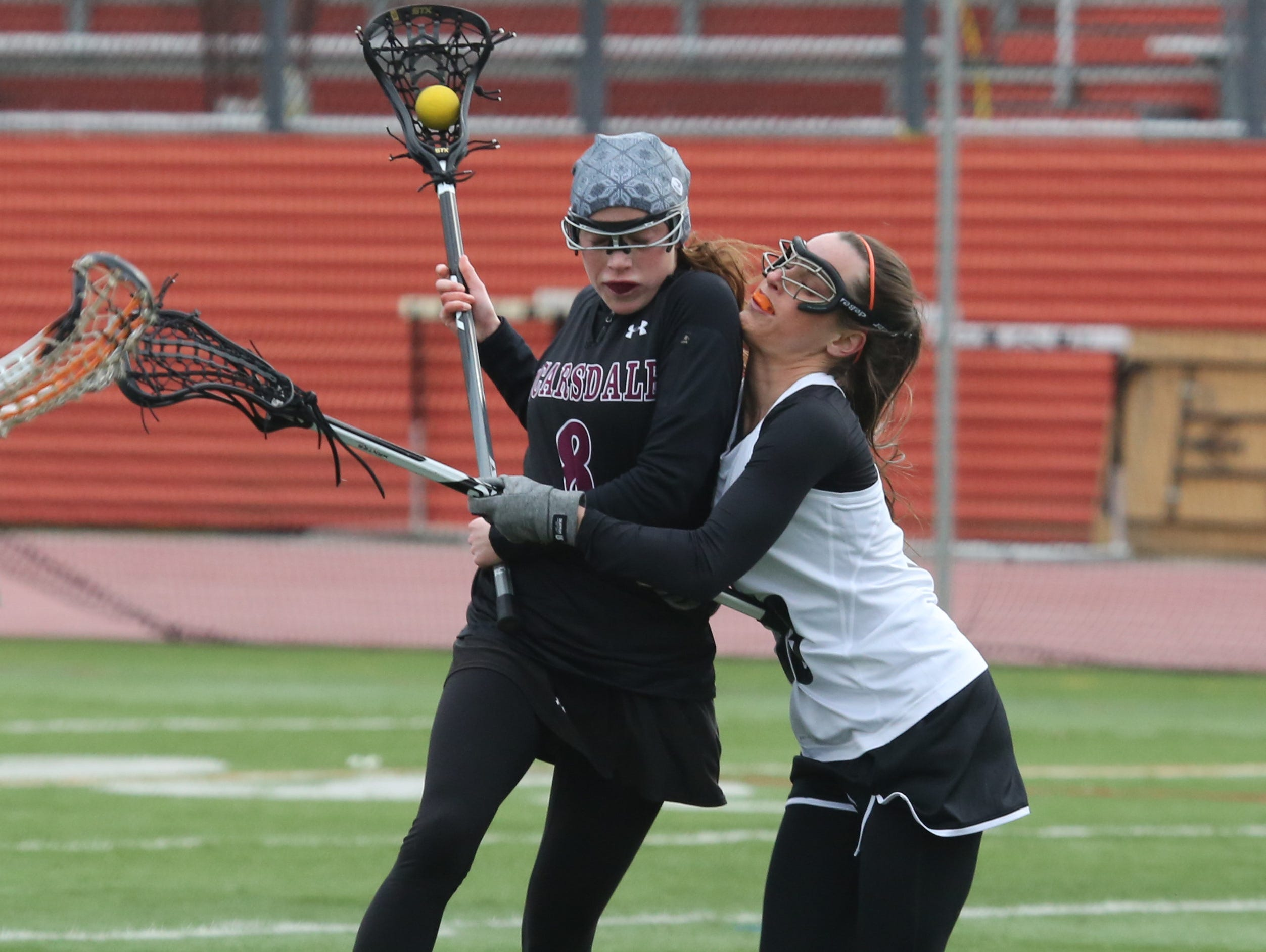 White Plains' Amanda Broderick puts pressure on Scarsdale's Jilly Mehlman during their girls lacrosse game at White Plains High School, April 6, 2016.