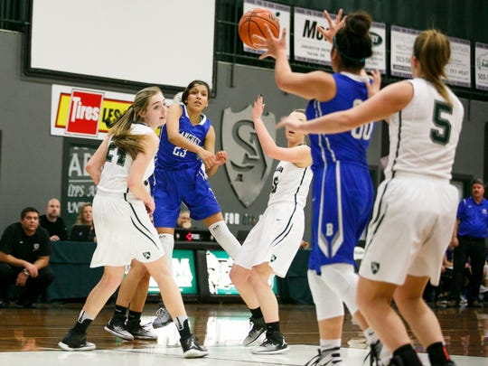 Blanchet's Ana Coronado (23) passes to teammate Kalea Salang (30) in a game against rival Salem Academy on Wednesday, Jan. 4, 2017 at Salem Academy. No. 4-ranked Blanchet defeated No. 1 Salem Academy 42-40 in the PacWest Conference game.