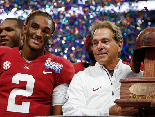 Alabama quarterback Jalen Hurts and Alabama head coach Nick Saban stand with the Leather Helmet trophy after an NCAA football game against Florida State, Saturday, Sept. 2, 2017, in Atlanta. Alabama won 24-7. (AP Photo/John Bazemore)