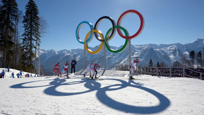Marit Bjoergen passes the Olympic rings as she leads Therese Johaug and Charlotte Kalla in the ladies skiathon during the Sochi 2014 Olympic Winter Games at Laura Cross-Country Ski and Biathlon Center.