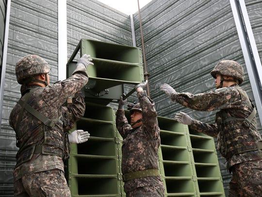 South Korean soldiers take down a propaganda loudspeakers