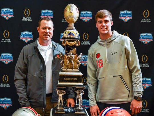 Former Milwaukee Brewers infielder Bill Spiers poses with his son, Will, a freshman punter at Clemson, and the Fiesta Bowl trophy. The elder Spiers is finishing his degree at Clemson and helping out with the football team.