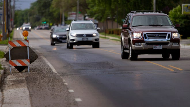 Motorists drive around a patched area of S. Commercial Street in Neenah.
