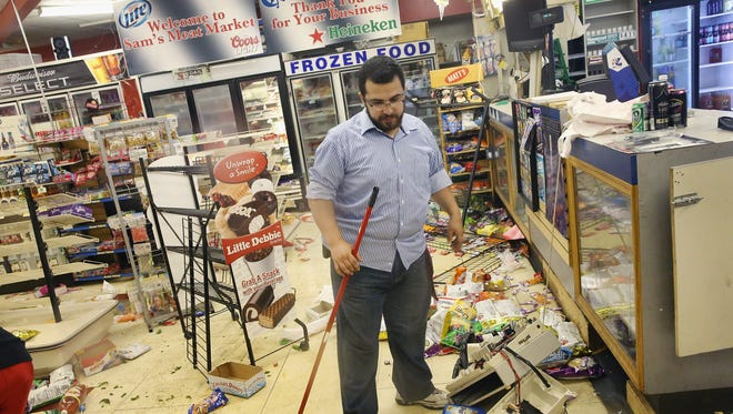 Ferguson business owner Mustafa Alshalabi cleans damage to his store, Sam's Meat Market, on Aug. 16 after it was looted during protests over the shooting death of Michael Brown.