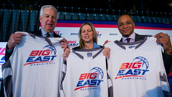 From left, basketball commentator Bill Raftery, Big East Commissioner Val Ackerman, and basketball commentator Gus Johnson hold jerseys  at a news conference during the Big East Conference NCAA college basketball media dayin New York, Wednesday, Oct. 16, 2013.