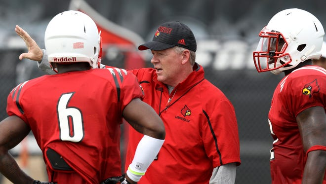 Coach Bobby Petrino talks with his team during practice. August 7, 2014
