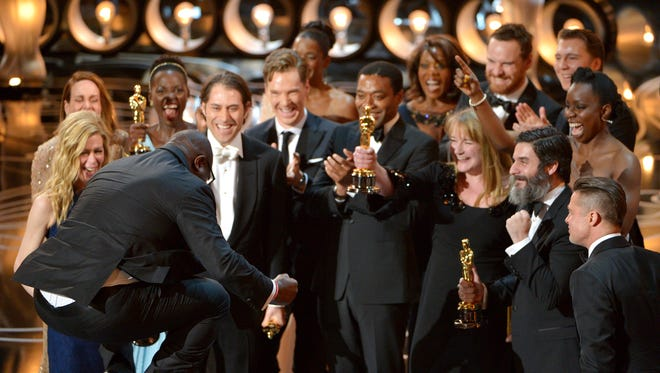 """Director Steve McQueen, left, celebrates with the cast and crew of """"12 Years a Slave"""" as they accept the award for best picture during the Oscars."""