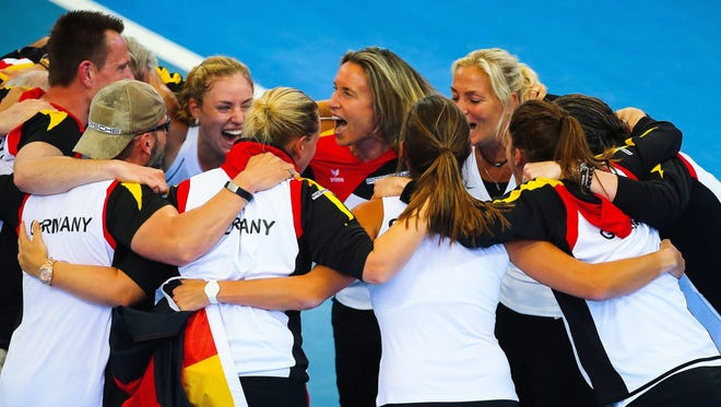 Members of Germany's Fed Cup team huddle together to celebrate their victory following the Fed Cup semi-final tie tennis match between Australia and Germany at Pat Rafter Arena in Brisbane on April 20, 2014. Angelique Kerber put Germany into their first Fed Cup final in 22 years with a fighting victory over Australia's Samantha Stosur in the semi-final in Brisbane.