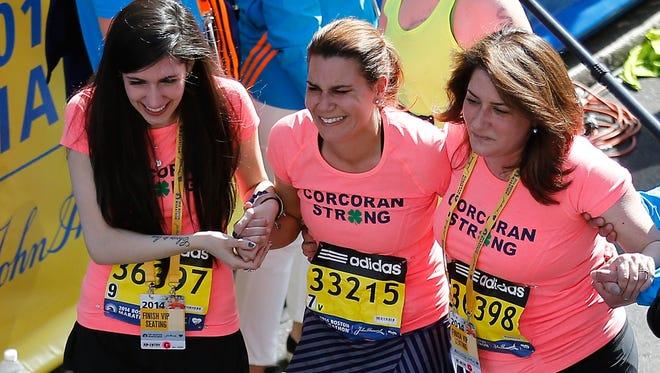 Boston Marathon bombing survivors Sydney Corcoran, left, and her mother, Celeste Corcoran, right, cross the finish line with Celeste's sister, Carmen Acabbo, at the 2014 B.A.A. Boston Marathon on April 21, 2014.  The Corcorans are survivors of the 2013 Boston Marathon bombing.