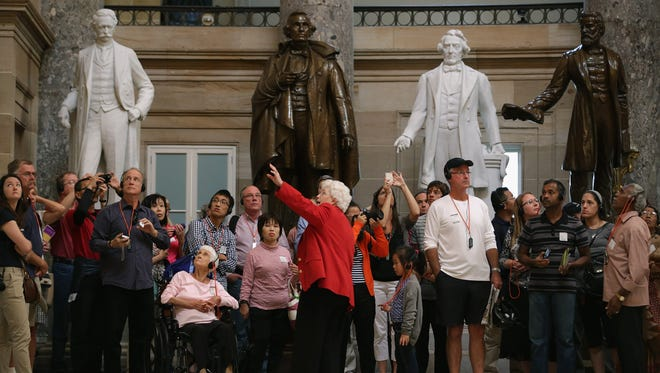 A guide leads a group of tourists through Statuary Hall at the U.S. Capitol in September.