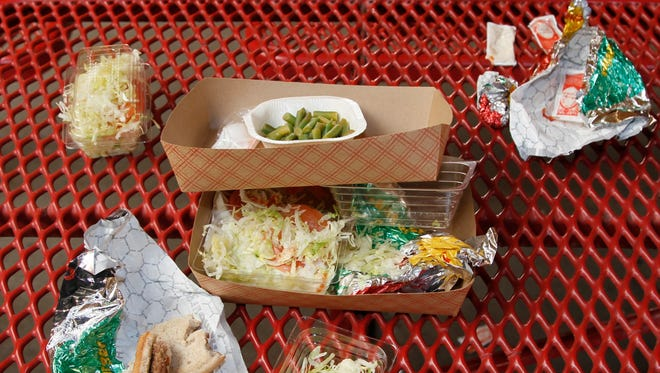 This 2012 file photo shows vegetables left over by students on their cafeteria trays at the Roosevelt High School in Los Angeles.