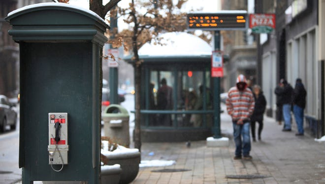 Pay phones are disappearing from the landscape because of cellphone popularity.  This one on Main Street in Rochester, N.Y., still survives.