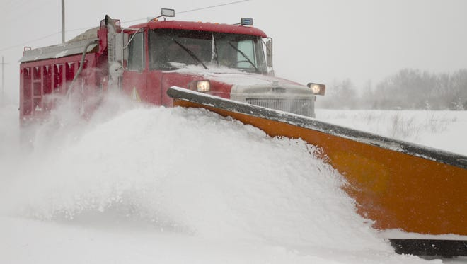 Brad Smith of the Livingston County Road Commission plows Runyan Lake Road south of Clyde Road in Hartland Township. Several schools have closed Monday.