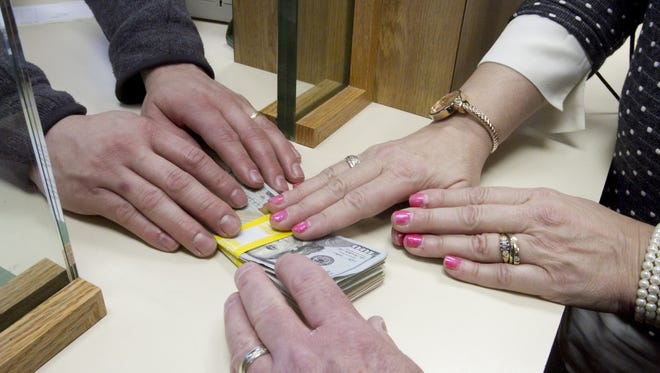 Money changes hands at Howell's First National Bank in this photo illustration.