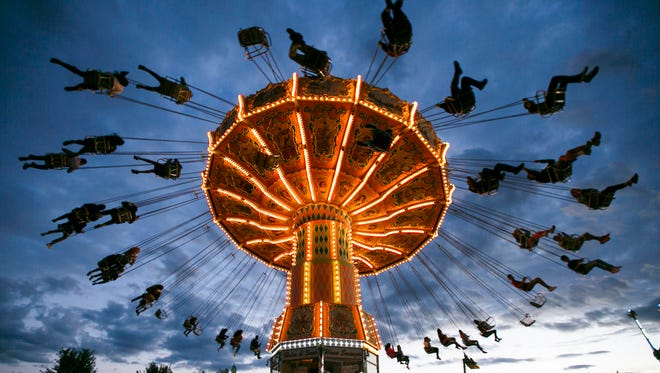 The Wave Swinger sends riders flying above the crowds at the Oregon State Fair on Sunday, Sept. 4, 2016. The ride formerly operated at Michael Jackson's Neverland Ranch.