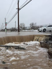 Water pours over the road at Dolores Drive and Pyramid