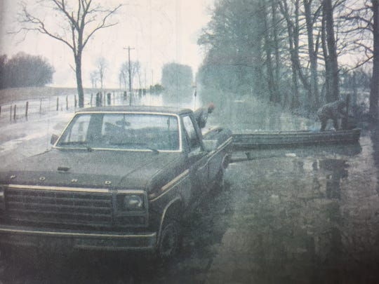 During the week of January 9th, 1991, heavy rains resulted in many flooded roads in Union County. Pictured are Bruce and Luther Kanipe bringing in a boat they used to check on property off Highway 1508.