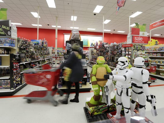 A customer pushes her cart down the aisle while shopping for Black Friday sales at Target.