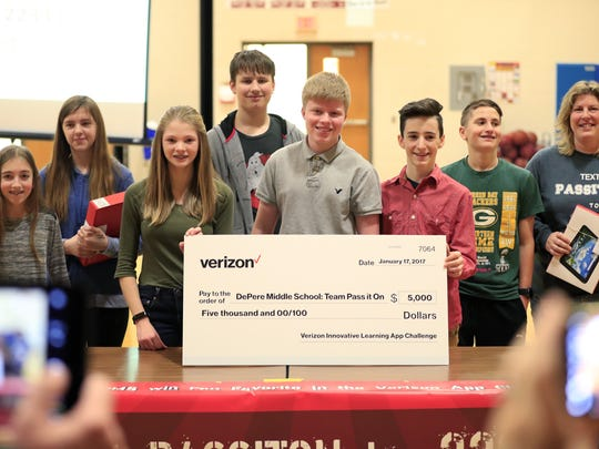 From left, De Pere Middle School students Annika Kennerhed, Hannah Janowitz, Amelia Sment, Maddox Terrien, Tyler Kraft, Noah Bomberg and Alex Foeller stand with computer literacy teacher Heather Wright after receiving a $5,000 check at the school Friday morning for winning a Best in State honor in the Verizon Innovative Learning app challenge.