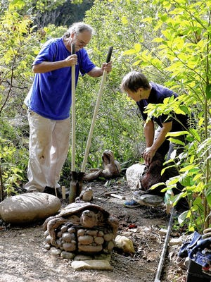 Dennis Deane takes a cache from a turtle created by his wife, artist Margaret McAdams, who was installing new works in Scioto Park in Dublin on Sept. 16.
