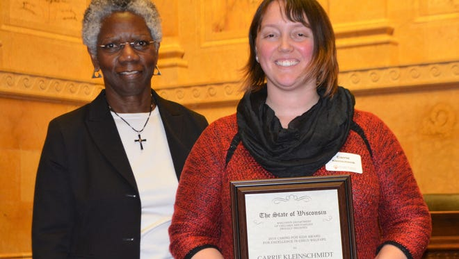 Oconto County child protective services supervisor Carrie Kleinschmidt, right, was presented with a 2018 Caring for Kids  award by Department of Children and Families Secretary Eloise Anderson, in a ceremony at the capitol in Madison on March 29, 2018.