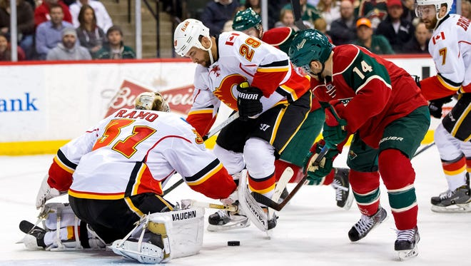 Calgary Flames goalie Karri Ramo (31) makes a save in the second period against the Minnesota Wild forward Justin Fontaine (14) at Xcel Energy Center.
