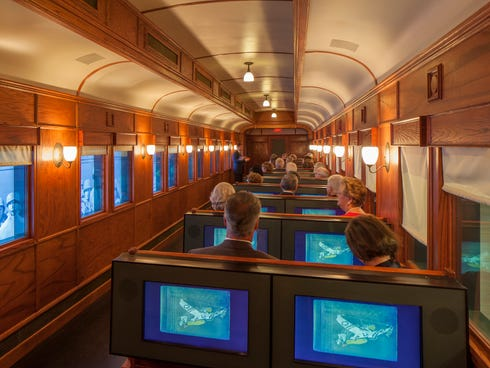 Video screens on the train car windows simulate traveling through the country. Vintage scrapbooks relate personal stories.