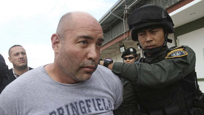 In this Sept. 26, 2013 file photo, Joseph Hunter, center, a former U.S. Army sniper who became a private mercenary, is in the custody of Thai police commandos after being arrested in Bangkok, Thailand. Hunter, already serving a 20 year term for plotting to kill a DEA agent, goes on trial in New York at the U.S. District Court in Manhattan Tuesday, April 3, 2018, on charges that he plotted to assassinate a real-estate agent for an international crime boss.