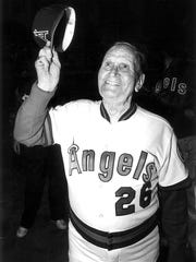 Gene Autry, owner of the Angels, tips his hat to the crowd while wearing the number 26 jersey the team retired in his honor