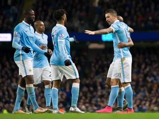 Manchester City's Aleksandar Kolarov, right, celebrates