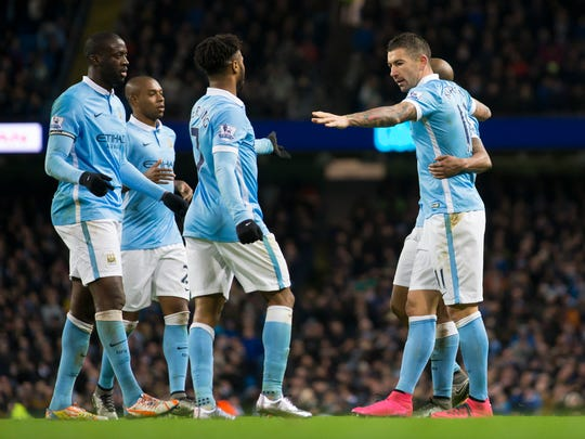 Manchester City's Aleksandar Kolarov, right, celebrates with teammates after scoring during the English Premier League soccer match between Manchester City and Southampton at the Etihad Stadium, Manchester, England, Saturday Nov. 28, 2015. (AP Photo/Jon Super)
