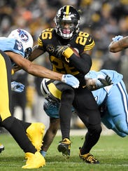 Steelers running back Le'Veon Bell (26) runs through the Titans defense in the second quarter.