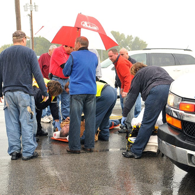 Good Samaritans and first responders tend to a pedestrian who was struck by a vehicle on West Perry and Jefferson streets around 12:50 p.m. Tuesday, Oct. 7.