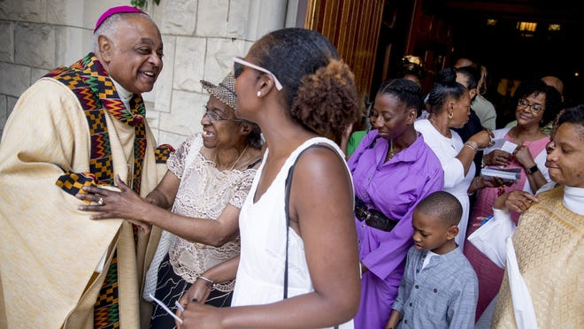 "Archbishop of Washington Wilton Gregory, left, greets parishioners following Mass last year at St. Augustine Church in Washington. In June 2020, Gregory, the first African-American in charge of the Archdiocese of Washington, joined with eight fellow bishops from his region to acknowledge the church's ""sins and failings"" in regard to racial justice."