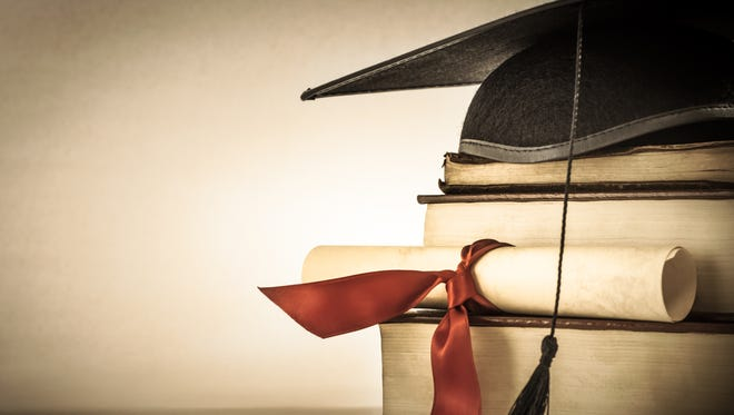 A mortarboard and graduation scroll, tied with red ribbon, on a stack of old battered books.