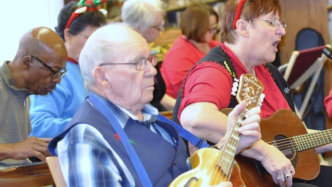 Franci Sims, of Crescent Springs, sings as she plays her dulcimer on Sunday, Dec. 13. At left is Harold Marsh of Verona. Both are members of the Hills of Kentucky Dulcimers, a group that has been been playing for crowds in the community for 22 years.