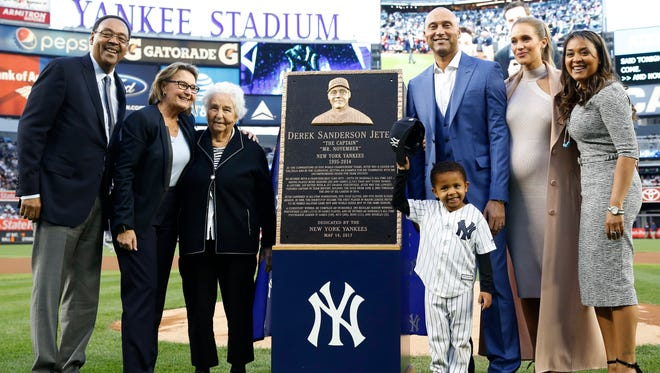Retired New York Yankees shortstop Derek Jeter third from right, poses with members of his family during a pregame ceremony retiring his number 2 in Monument Park at Yankee Stadium in New York, Sunday, May 14, 2017. The plaque is a replica of the one installed Monument Park. (AP Photo/Kathy Willens, Pool)
