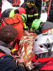 A woman gets assistance after being pulled out from the hotel that was hit by an avalanche on Wednesday, in Rigopiano, central Italy, Friday, Jan. 20, 2017. Rescue crews located more than eight people alive in the rubble of an avalanche-crushed hotel on Friday, an incredible discovery that boosted spirits two days after the massive snow slide buried around 30 people in the resort.